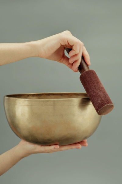 Person running pestel around golden bowl to make vibrations