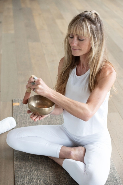 woman in white sitting on yoga mat uses pestel and bowl to make vibration sounds