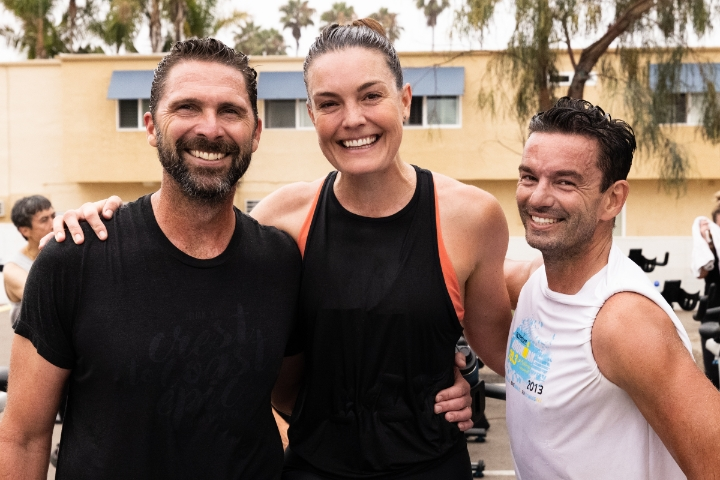 Two men with woman in middle after a workout