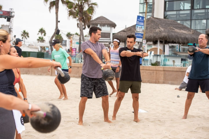 Group working out using kettle bells with fitness trainer