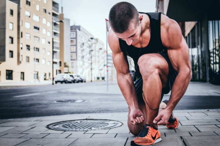 muscular guy in black tank top tieing shoe lace of orange shoes